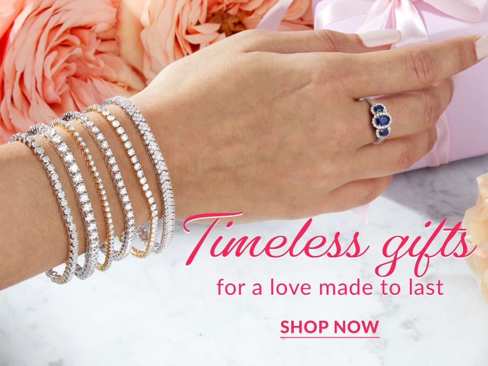 timeless gifts for a love made to last. shop now. background image features a woman reaching for a gift, wearing multiple diamond tennis bracelets and a three-stone sapphire ring