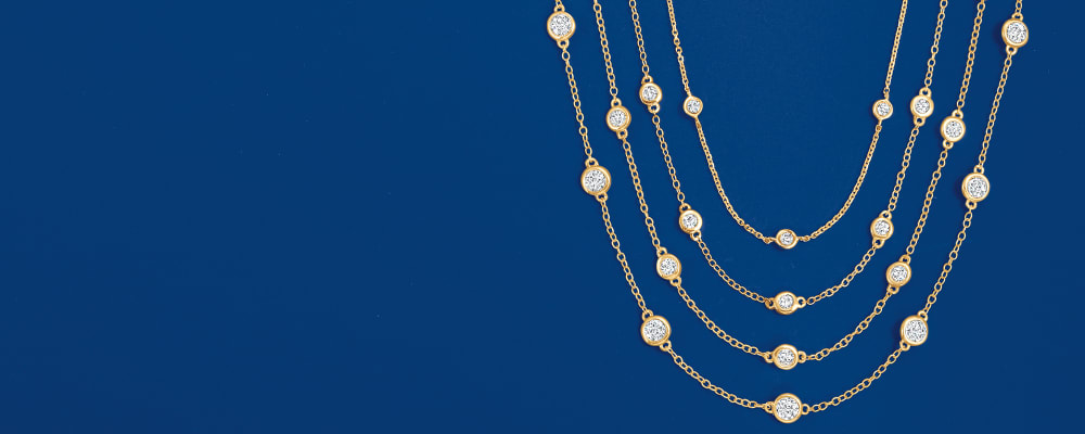 Diamond station necklaces. indulge in timeless sparkle. Image Featuring Diamond Station Necklace on Deep Blue Background