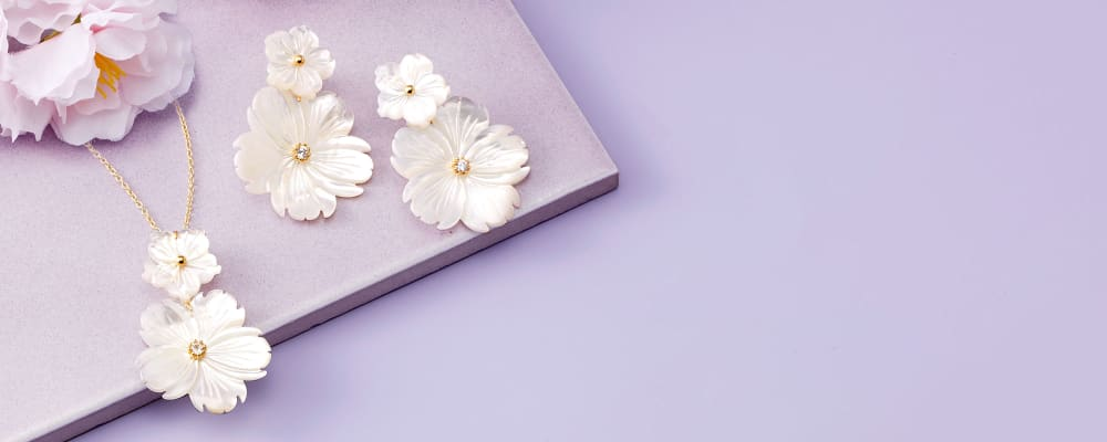 Spring Thing. Styles Inspired By The New Season. Image Featuring White Floral Jewelry on Purple Background