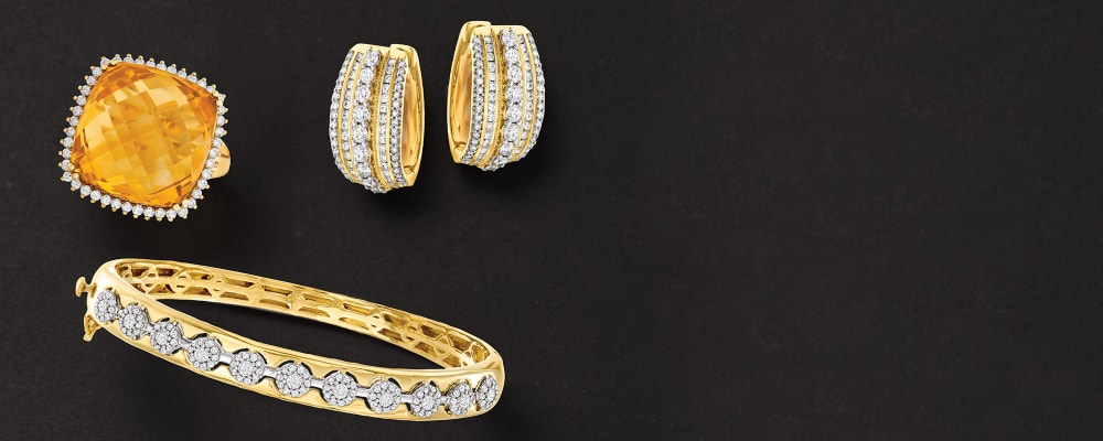 Stunning Jewelry. Fabulous Finds At Our Always-Low Price. Image Featuring Assorted Gold and Diamond Jewelry on Black Background