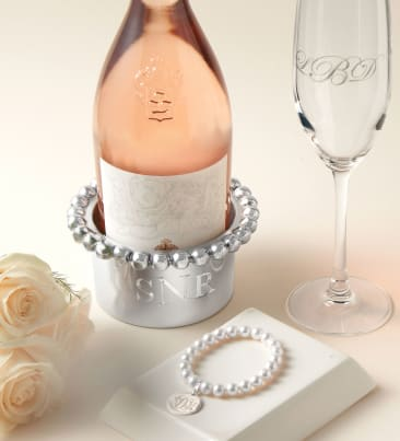 The Personal Touch. Unique ways to remember the day. Image of wine bottle, wine holder, wine glass and pearl bracelet.