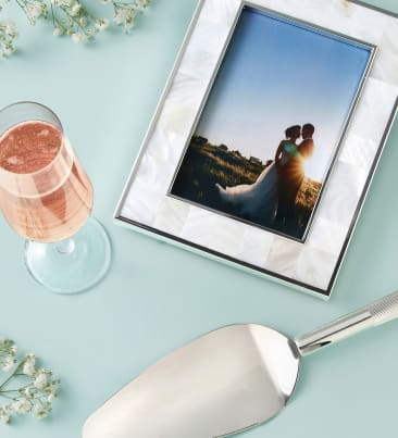 Gifts to cherish. Lasting memories for the happy couple. Image of champagne glass, picture frame and cake knife.