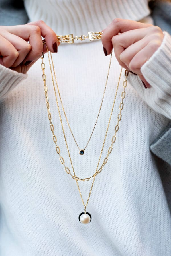 Model holding three gold necklaces. Products 923629, 913578, 926742 and 900733.