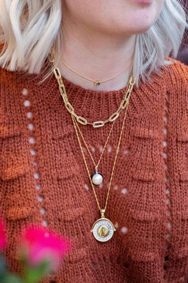 Model wearing gold necklace and two pendants. Products 926742, 929177, 913578 and 900733.