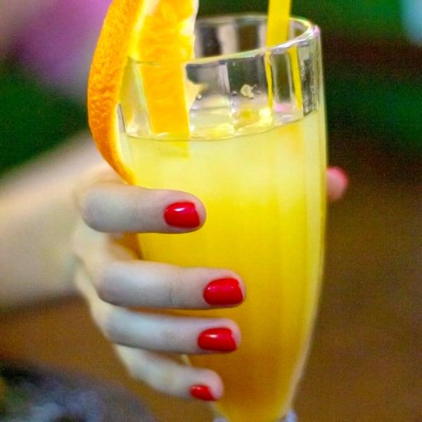 Hand with red nail polish holding range spritz beverage. Photo by Oleg Gospodarec on Unsplash.com