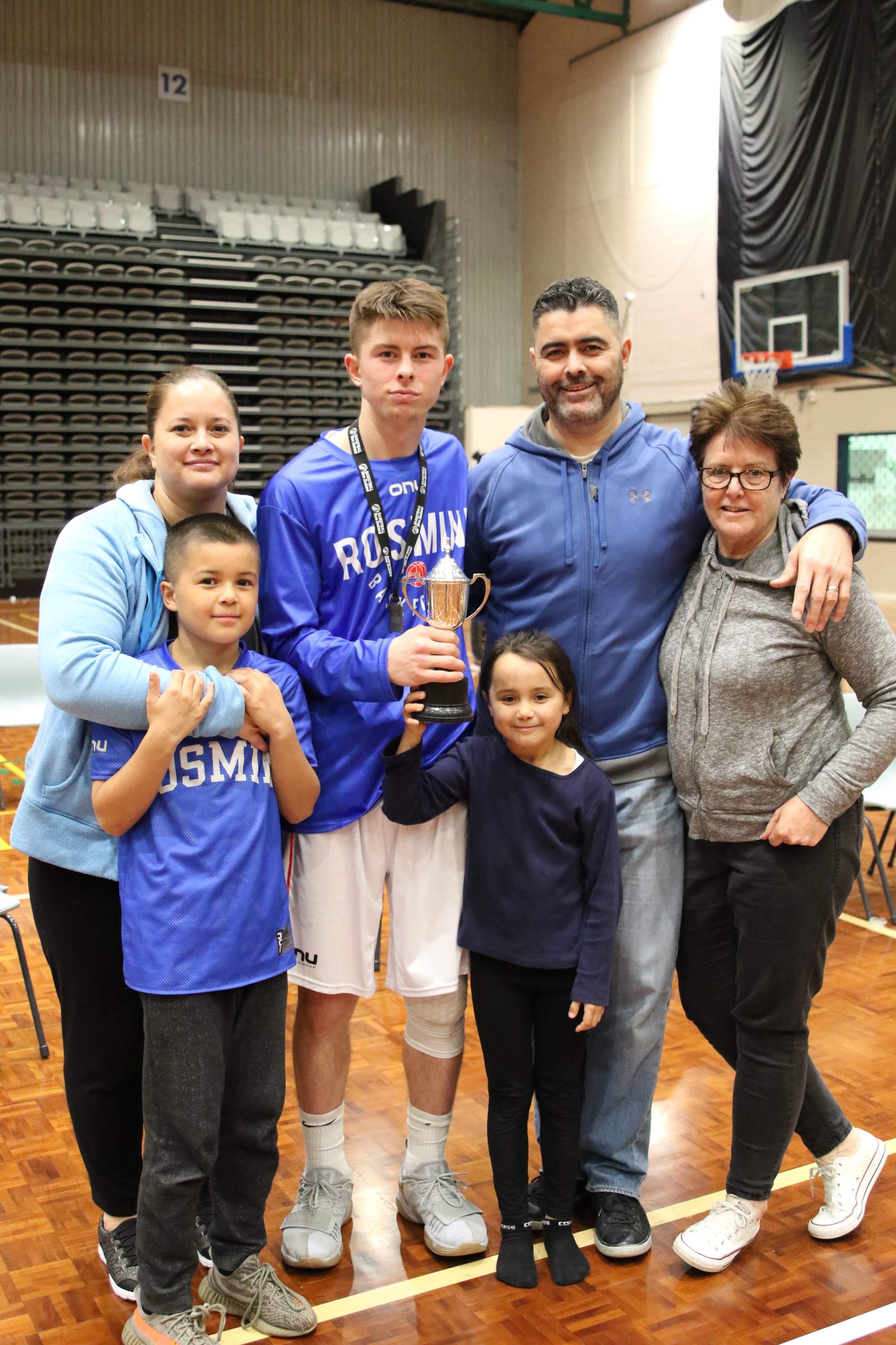Kainoa with his family, holding a trophy