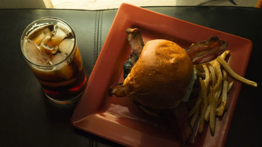 Bacon hamburger with french fries on a red square plate and a glass of whiskey on a leather seat