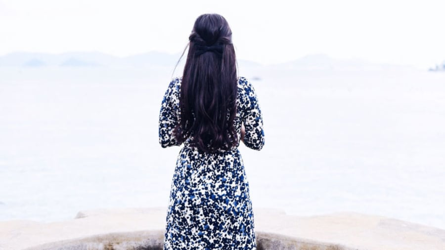 ​Woman with long black silky hair tied with a bow wearing a long blue and white floral dress