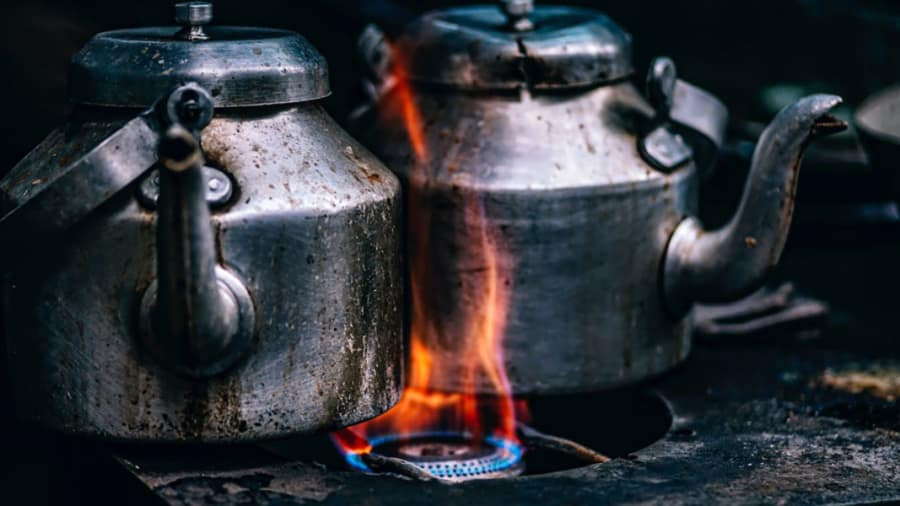 Two old kettles boiling on the stove
