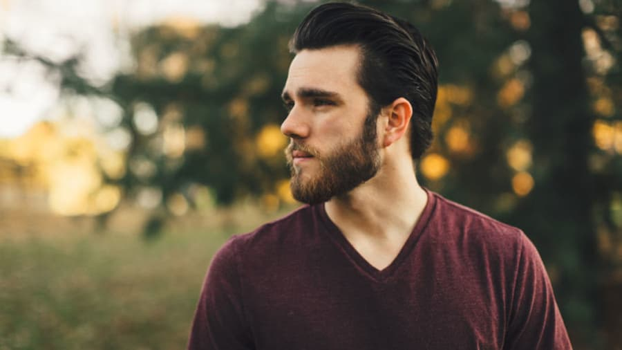 Man in field about to shave his beard without getting razor burn