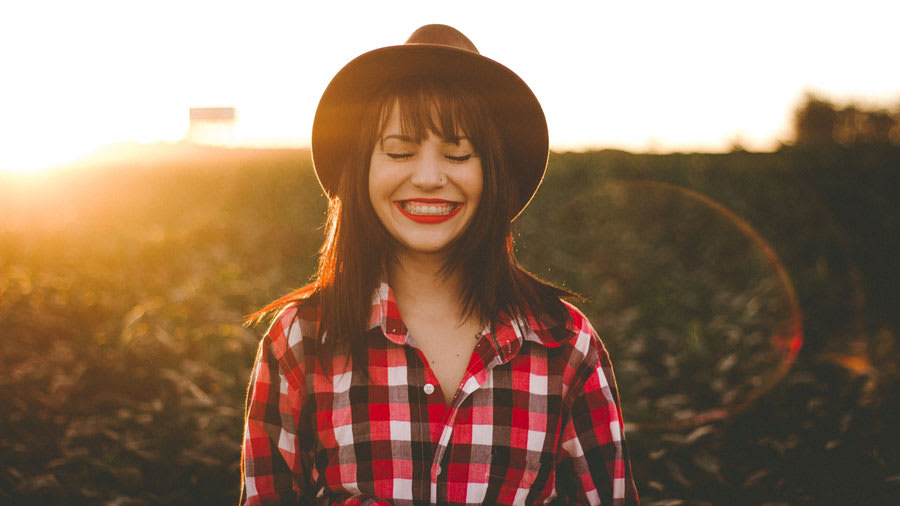 Woman with hat and plaid shirt and red lipstick smiling outside with sunset behind her