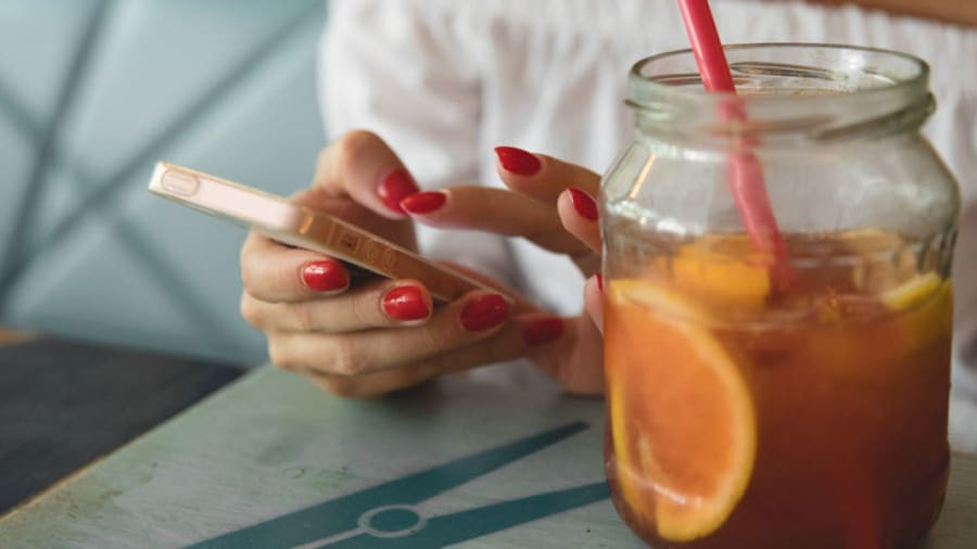 Woman with red manicured nails drinking tea for nutrition
