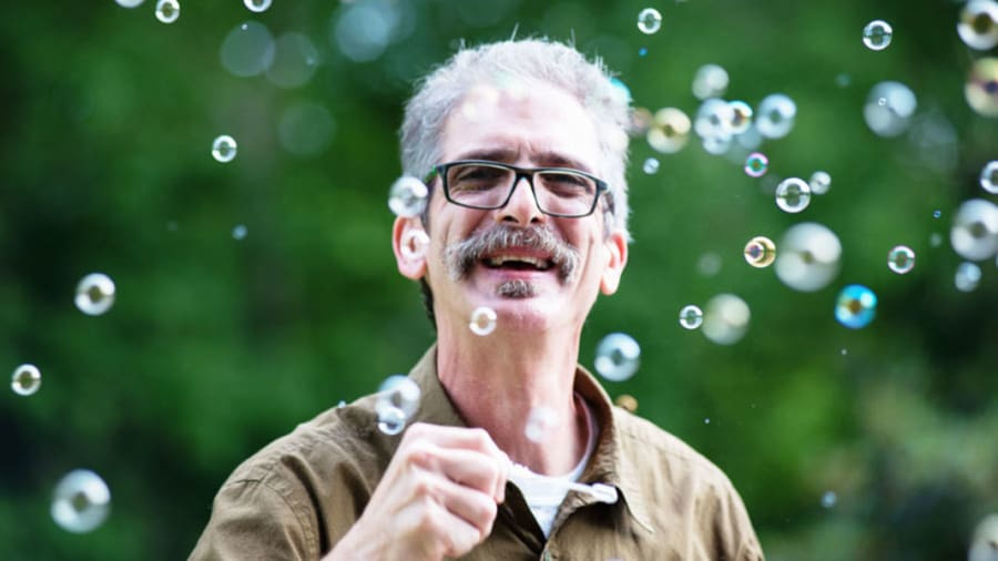 Man with gray hair surrounded by bubbles