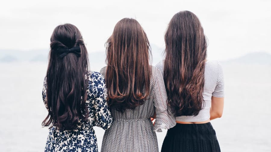 Three women with long hair standing next to each other