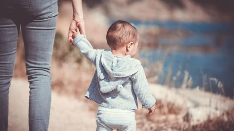 Child with blue hoodie walking on beach while holding an adult's hand