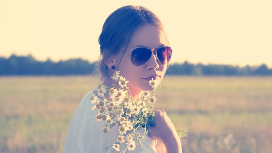 Woman with sunglasses outside in sunshine holding flowers