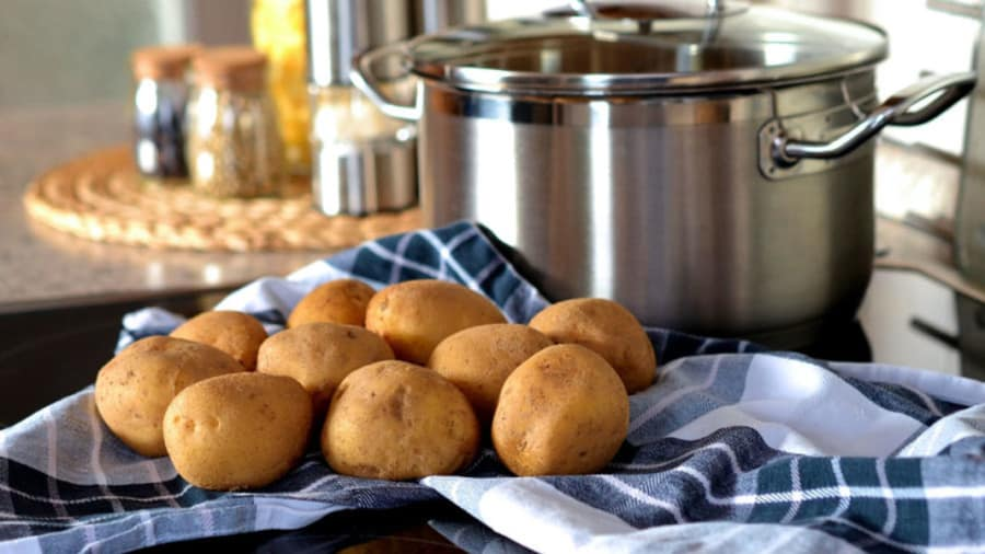 Potatoes boiled and cooled on a towel on a table in kitchen next to boiling pot