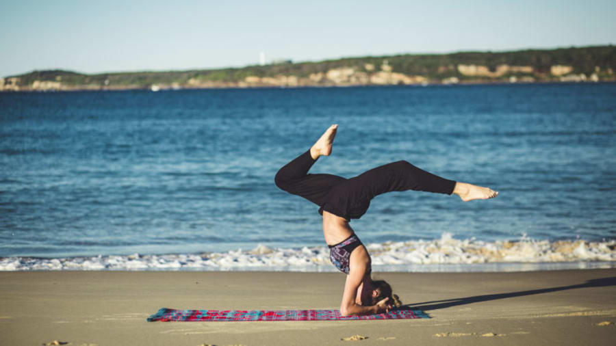 Woman performing yoga in black leggings and on the beach with water in background