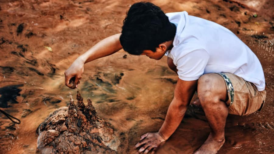 Young barefoot man playing with mud