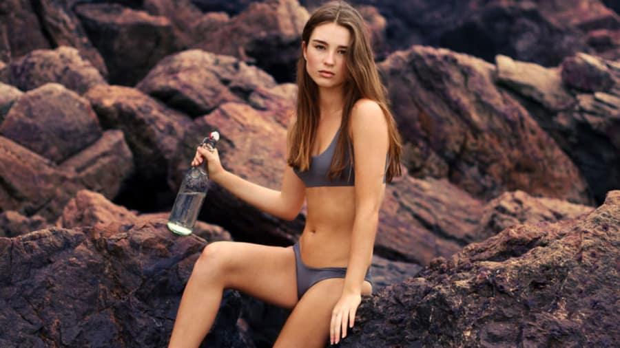 Beautiful woman wearing bikini holding water bottle sitting by rocks