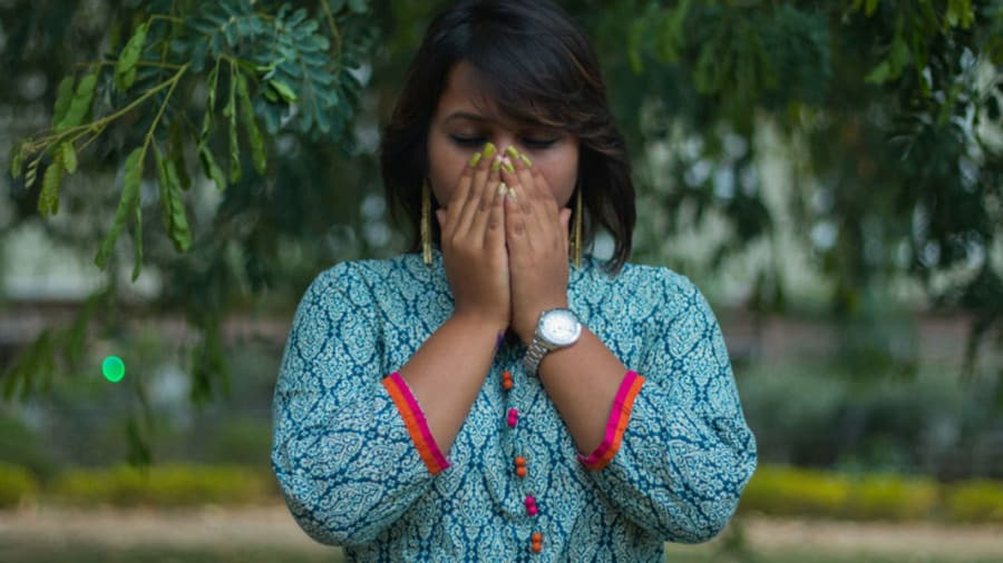 Indian woman with dark skin wearing turquoise blouse and watch covering mouth and nose with eyes closed