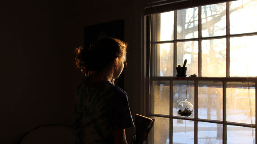 Depressed woman looking out of a window