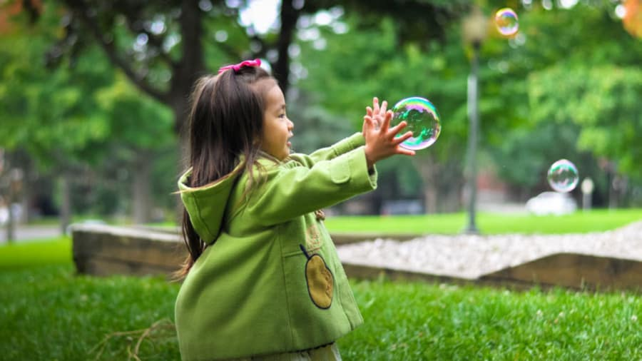 Asian girl wearing green jacket playing with bubbles in a park