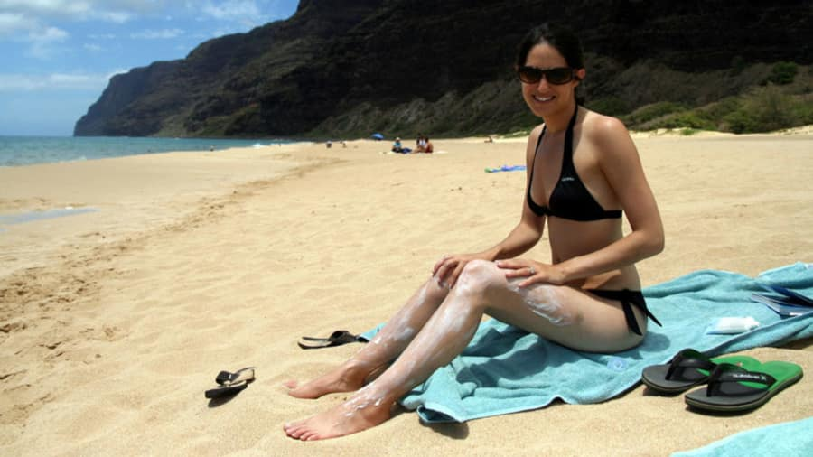 Brunette woman applying sunscreen to her shoulder