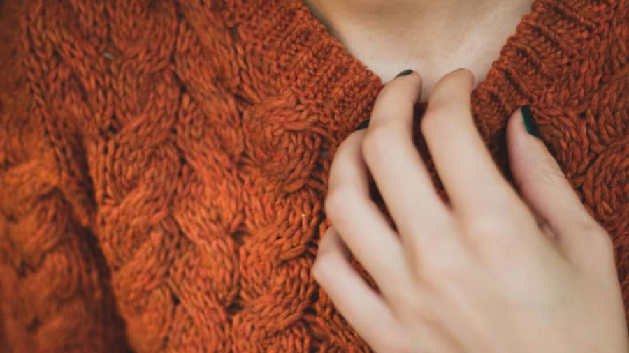 close-up of woman with dark green manicured nails wearing orange wool sweater scratching neck