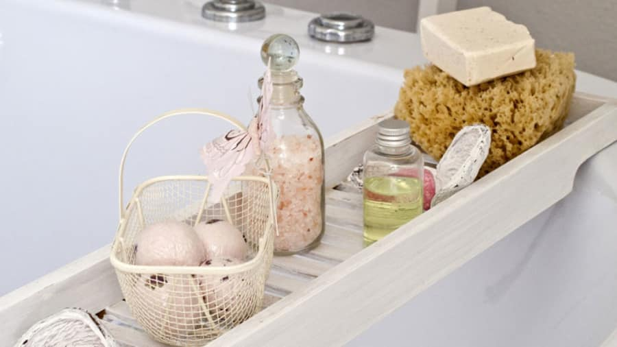 Bath oil and bathing amenities next to a bathtup