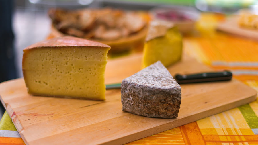 Assorted cheeses and and knife on a wooden cutting board