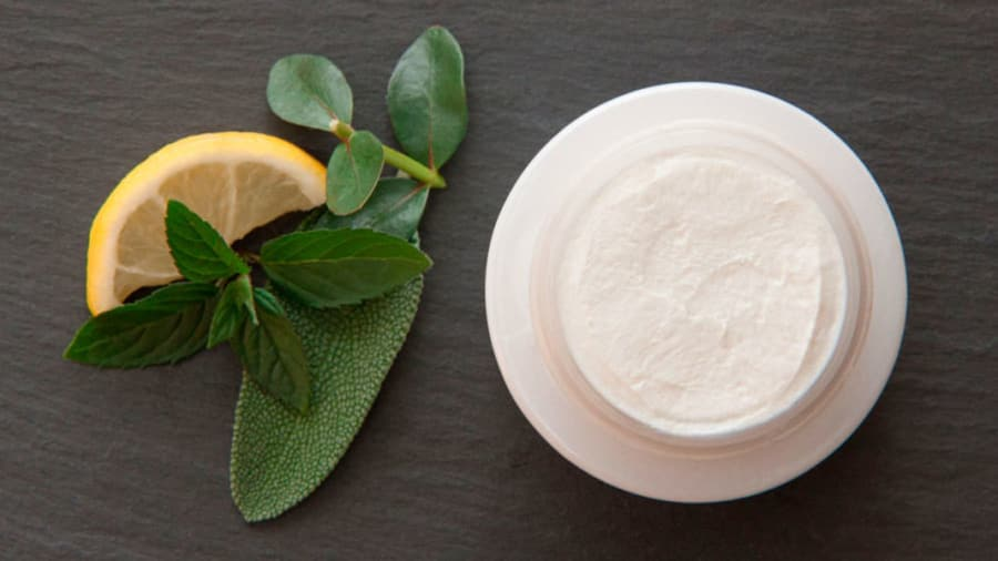 Lemon with some leaves next to top view of skin cream on a wooden table