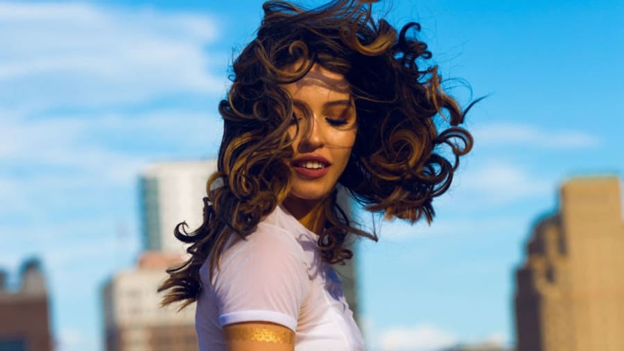 Woman with her curly brown hair blowing in the wind