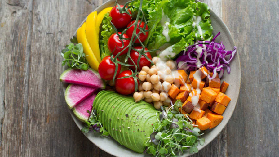Multiple colorful plant based foods on a plate on a wooden table