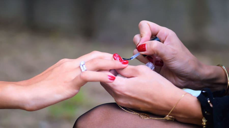 Red nail polish being applied during a manicure