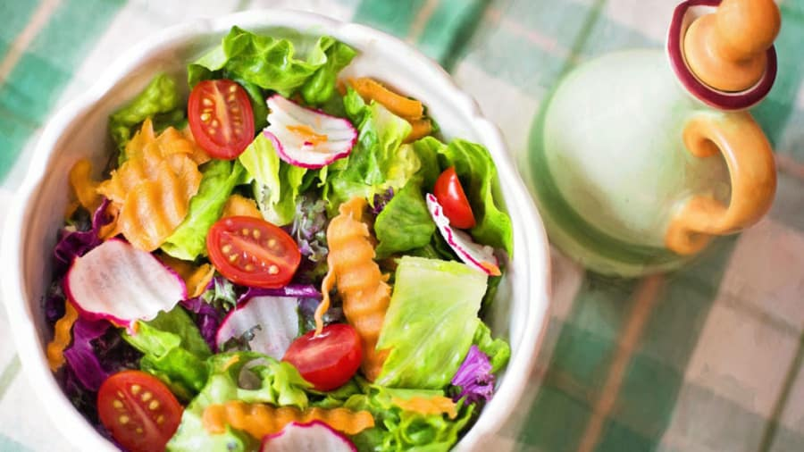 ​colorful vegetable salad lettuce radishes grape tomatoes carrots on checkered tablecloth