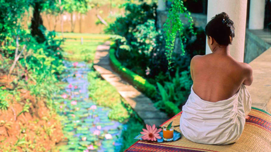 woman in Sri Lanka sitting outside near pillar next to gentle stream filled with lotuses