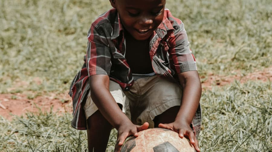 ​black-child-wearing-red-plaid-shirt-and-cargo-shorts-bending-down-to-play-with-soccer-ball