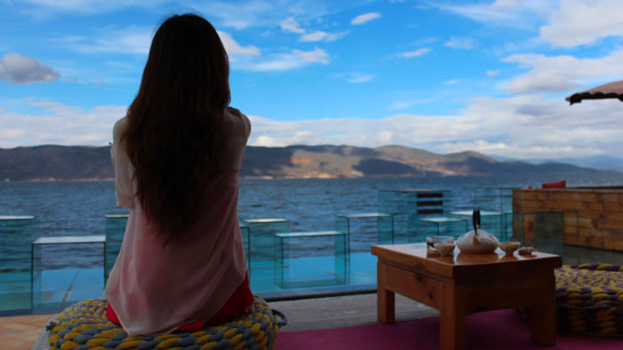 Woman sitting at resort and looking at water with rolling hills