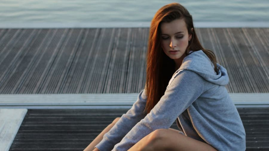 Pretty woman sitting and pensive wearing a hoodie