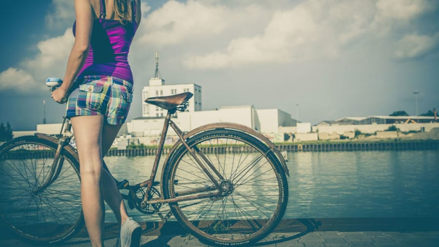 woman wearing  plaid shorts and purple shirt holding beach cruiser by river bed