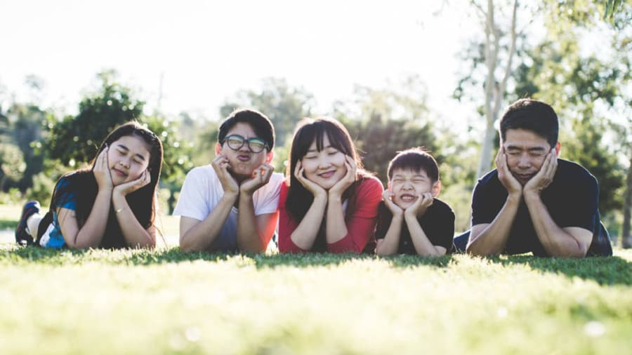 asian family laying on grass making silly funny faces