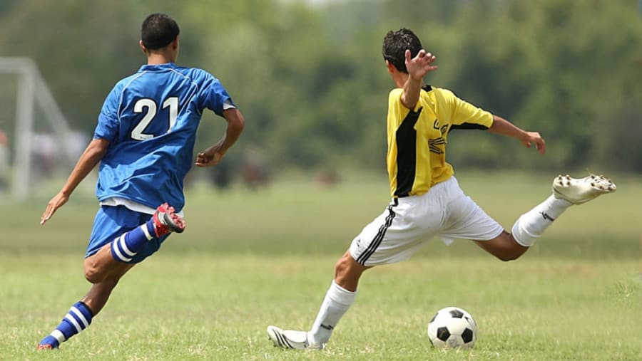 Soccer players in blue and yellow jerseys kicking soccer ball