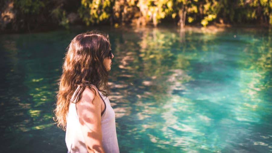 Brunette woman with sunglasses standing in sunshine next to blue pond