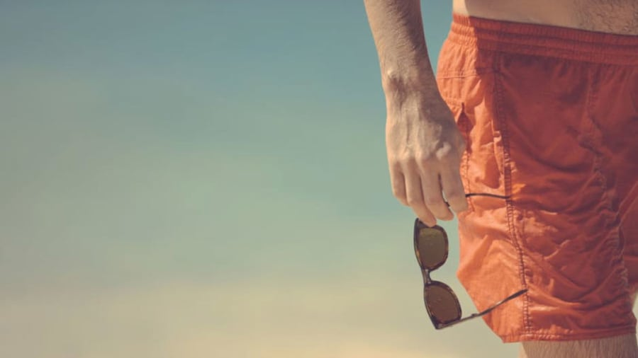 Man holding sunglasses wearing an orange swimsuit on beach