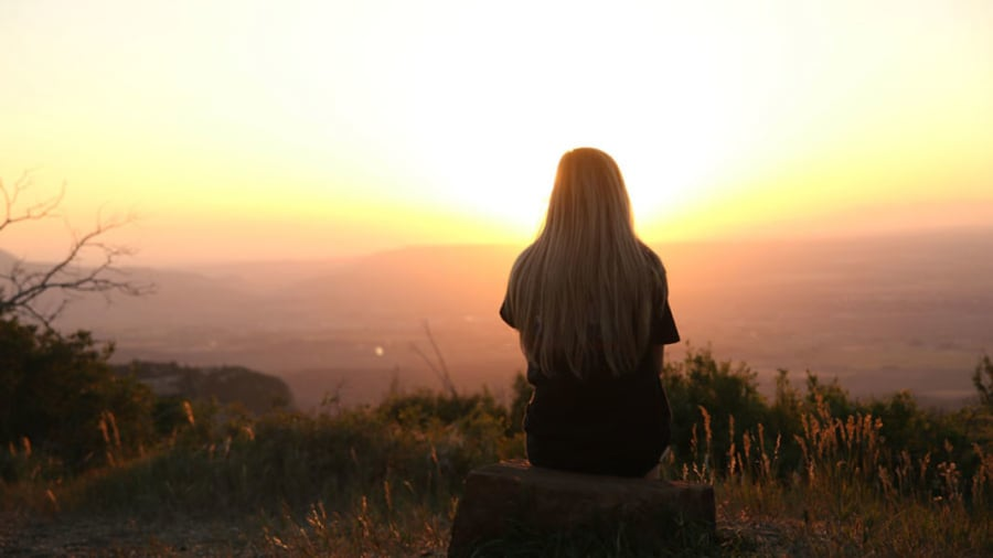 Woman looking over a city from hill with sunset over hills