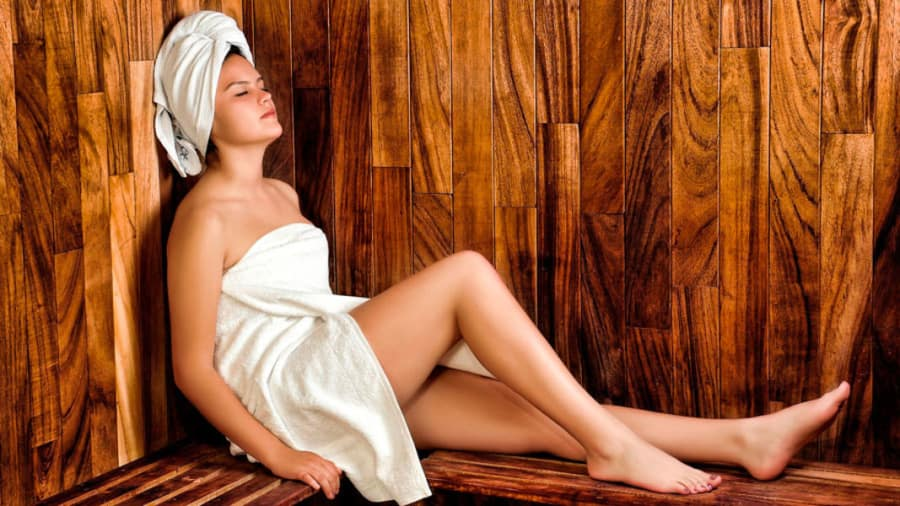 Woman wrapping in white towel sitting in sauna