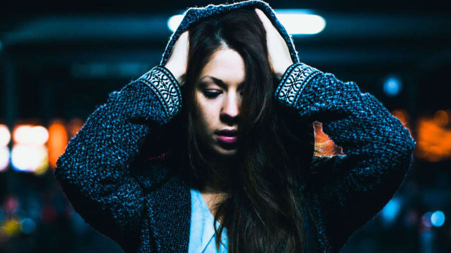 Woman holding her head and covering up with hoodie at night