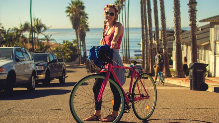 Woman with bicycle in middle of road in city near beach in background