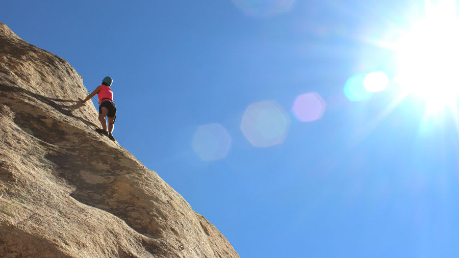 woman rock climbing under hot sun